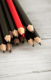 Red pencil stands out from the crowd of black  on a wooden white background. Stock Photos