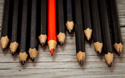 Red pencil stands out from the crowd of black  on a wooden white background. Stock Photography