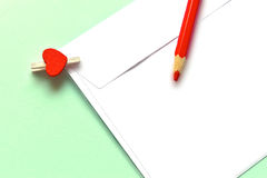 Red pencil and tiny clothespin holding a white envelope. On turquoise background Royalty Free Stock Photos