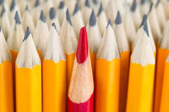 Red pencil tip in stack of regular pencil tips Royalty Free Stock Image