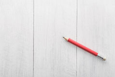 Red pencil on wooden white Royalty Free Stock Photo