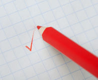 Red pencil writing a mark Stock Photos