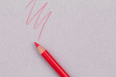 Red pencil and zigzag line on beige pastel paper coarse grain grunge texture. Try a pencil line royalty free stock image