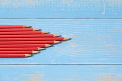Red pencils of arrow shape on blue wooden background stock photo