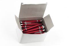 Red pens in a white box. Red pens in a white cardboard box stock photo