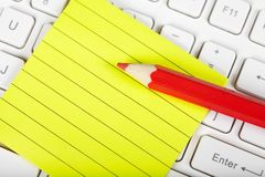 Red pensil and keyboard Stock Photo