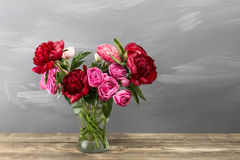Red peonies and garden roses in vase. retro styled photo. close-up Royalty Free Stock Images