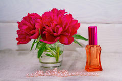 Red peonies, perfume bottle,  beads Royalty Free Stock Photo