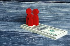Red people and a child are standing on a pile of dollars. People stand on the money. Paying taxes, receiving benefits. Family. Savings, investments in new Royalty Free Stock Photos