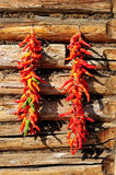 Red pepper. Manufacture of wood on the walls hung two strings of red-hot red pepper Royalty Free Stock Photo