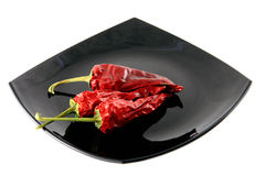 Red pepper. Pods of dried red pepper on a plate stock photos