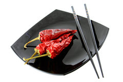 Red pepper. Pods of dried red pepper on a plate royalty free stock photography