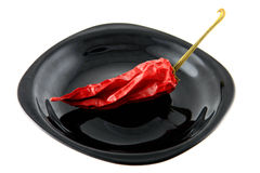 Red pepper. Pod of dried red pepper on a plate stock images