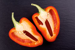 Red pepper cut into two parts on dark stone Stock Photos