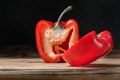 Red pepper cut into two pieces on wooden cutting board Stock Photography
