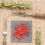 Red pepper on dark plates with rosemary and antique fork. Red peppercorns on dark plate with rosemary and antique fork. Rustic background. Warm color. Square Stock Images