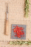 Red pepper on dark plates with rosemary and antique fork Stock Photos