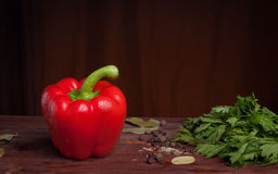 Red pepper on dark wood background with herbs. And spices Stock Photo