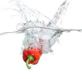 Red pepper falling into water over white Stock Photo