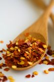 Red pepper flakes. On a wooden spoon over following Stock Photography