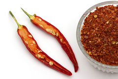 Red pepper flakes and fresh red hot chili peppers Royalty Free Stock Photos