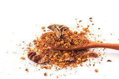 Red pepper flakes in wooden spoon on white Stock Image