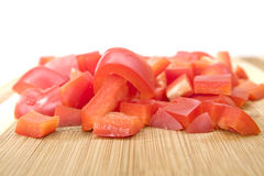 Red pepper, fresh and sliced on chopping board Stock Photos