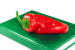 Red pepper on a green book Royalty Free Stock Image