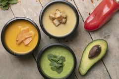 Red pepper,half avacado and spoon near vegan soups in food containers, ready meal to eat royalty free stock images
