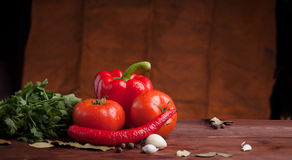 Red pepper, herbs and spices on dark wood. Table with grunge background Royalty Free Stock Image