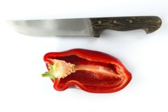 Red pepper and kitchen knife over white Royalty Free Stock Photo