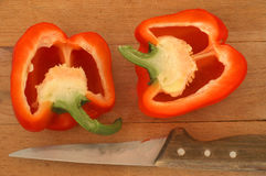 Red pepper and a knife. Red pepper on a slice board, sliced by halves Royalty Free Stock Photography