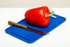 Red pepper and a knife Stock Photography