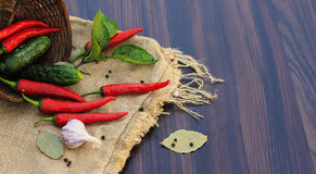 Red pepper with leaves on sacking on the table with a basket Stock Images