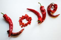 Love, burning passion. Red pepper lined with the word love. White background, copy space. Passionate relations, hot feelings. Spice, piquancy, passion royalty free stock images