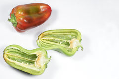 Red pepper and other one, green, cut in half Royalty Free Stock Photo