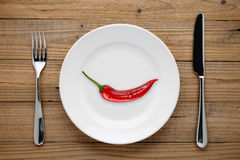 Red pepper on plate, fork and knife on wood Royalty Free Stock Photography