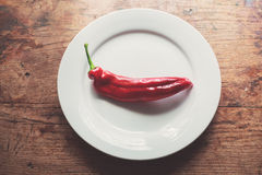 Red pepper and a plate. Large red pepper and a plate on a wood table in the sunlight Stock Photography