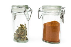 Red pepper powder and  dried basil in jars Royalty Free Stock Photography