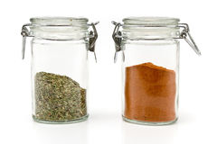 Red pepper powder and oregano in jars Stock Photography