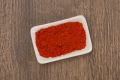 Red pepper powder over wood background royalty free stock photography