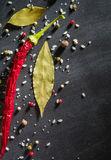 Red pepper pungent spices and bay leaf on the black tree. View from above. Space for text stock photos