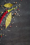 Red pepper pungent spices and bay leaf on the black tree. View from above. Stock Photo