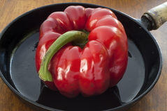 Red pepper ready for roasting in a black, iron pan. Royalty Free Stock Image