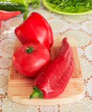 Red pepper, red pepperoni and a red tomato on a wooden plate and decorated cover - front view Royalty Free Stock Photography