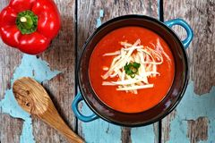 Red pepper soup overhead scene on rustic blue wood background Royalty Free Stock Photos