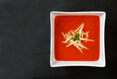 Red pepper soup in a square bowl on slate Royalty Free Stock Photos