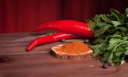 Red pepper and spices on wood desk. Chili pepper on a wood table with herbs and spices on wood slice Stock Image