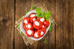 Red Pepper stuffed with cheese on wooden background selective. Filled Pimientos on an old wooden table as detailed close-up shot selective focus Royalty Free Stock Photo
