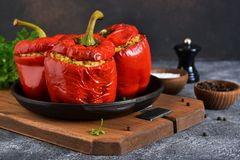 Red pepper stuffed with meat, bulgur and vegetables in a cast-iron pan. Baked stuffed peppers royalty free stock photo